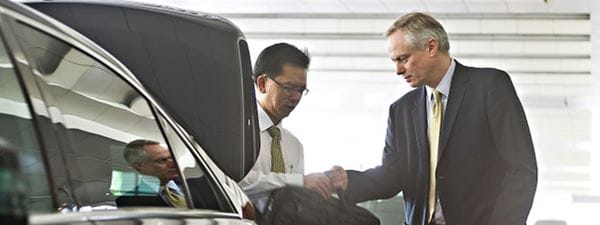 Business traveller getting in to car